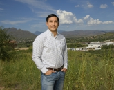 Jose R. Soto, assistant professor in the School of Natural Resources and the Environment, stands along the U.S.-Mexico border overlooking a produce-trucking facility.