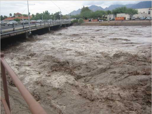 The Rillito 'River' of Tucson in flood stage, with water almost up to the bottom of the Campbell Avenue Bridge.