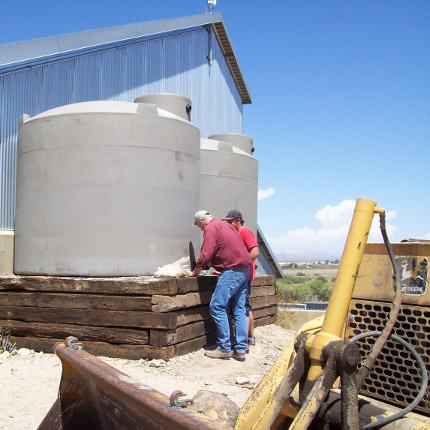 Extern Tyler Pearce helps Graham County Cooperative Extension Director Bill Brandau install the plumbing for a rainwater harvesting tank at Eastern Arizona College's Discovery Park in Safford. Pearce was also responsible for designing a landscape plan for Discovery Park that will make the most efficient use of harvested rainwater.
