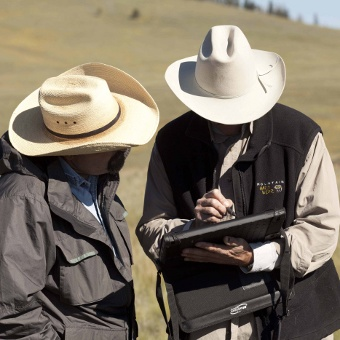 Two range specialists using a computer tablet to collect monitoring data in the field. (Photo by Scott Baxter)
