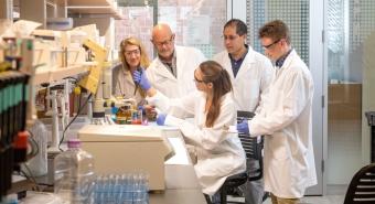 Members of Ski Chilton's lab surround a microscope