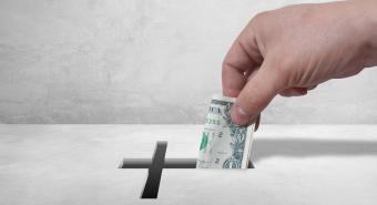 A hand slipping a dollar into a church donation box